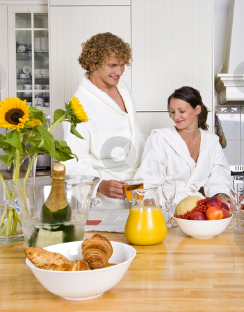 Mornin tea stock photo, Young couple enjoying a sunday champagne breakfast with tea, croissants, champagne and assorted fruits on a kitchen counter by Corepics VOF