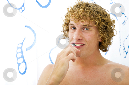 Brushng Teeth stock photo, Young man brushing his teeth looking at the camera by Corepics VOF