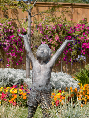 Happy statue stock photo, A joyful garden statue of a child in shorts. by Cora Reed