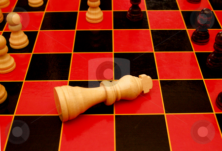 The king is dead. stock photo, King piece on a chess board in the draw position. by Cora Reed
