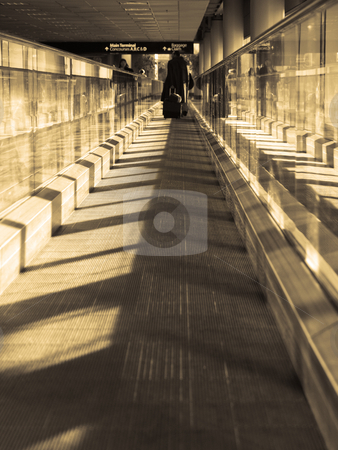 Moving sidewalk stock photo, Moving walkway in an airport, with light streaming in in sepia by Cora Reed