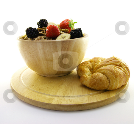 Bran Flakes in a Wooden Bowl stock photo, Crunchy looking delicious bran flakes and juicy fruit in a wooden bowl with a croissant on a white background by Keith Wilson