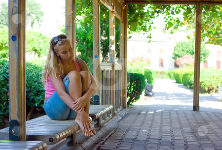 Girl on the bench stock photo, Beautiful blonde girl sitting on the bench in the park by Dmitry Rostovtsev