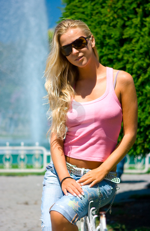 Blonde at the fountain stock photo, Beautiful blonde girl standing at the fountain by Dmitry Rostovtsev
