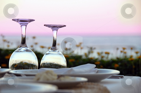 Table for dinner stock photo, Outdoor table with wine glasses over magenta sky by Julija Sapic