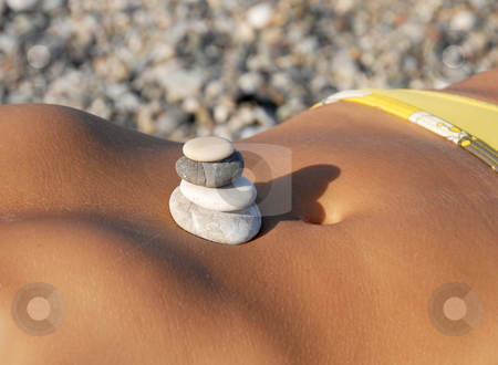 Rocks stack on stomach stock photo, Rocks in stack on woman sunburnt by Julija Sapic