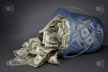 Bucket-O-Bucks empties out stock photo, Large blue transparent plastic bucket filled with dollar bills on its side, money spilling out by James Barber
