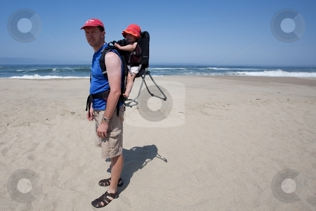 Child carrier on the beach stock photo, Child carrier is a device used to carry an infant or small child on the body of an adult. by Mariusz Jurgielewicz