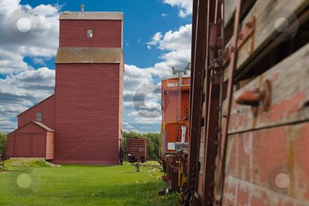 Prairie Farm Life stock photo, A train travelling on the tracks by a prairie grain elevator by Richard Nelson