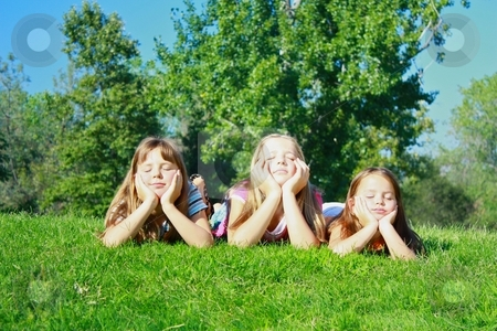 Girls lying on grass stock photo, Girls lying on grass by Gregory Dean