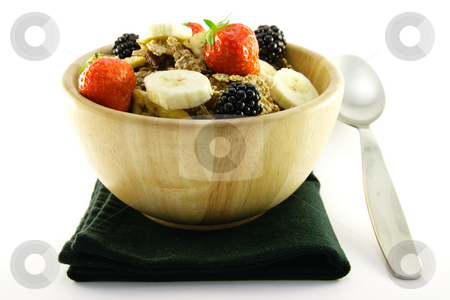 Bran Flakes in a Woodden Bowl stock photo, Crunchy delicious looking bran flakes and juicy fruit in a wooden bowl with a spoon and a black napkin on a white background by Keith Wilson