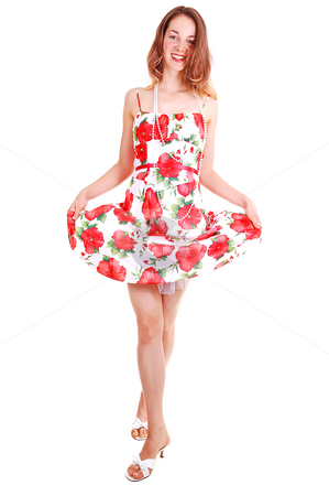 Woman lifting up her dress. stock photo, Lovely young woman in high heels standing in the studio with long brown hair and lifting up her colorful dress, shooing her nice legs. by Horst Petzold