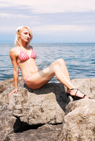 Bikini girl on the rocks. stock photo, A blond young woman in an red and white bikini sitting on the rocks to get a nice tan and shooing her slim body. by Horst Petzold