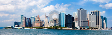 New York City Skyline panorama stock photo, Panorama of the famous landmark view of the Manhattan New York City Skyline with the Financial district, World Trade Center and Wall Street. NYC known as the Big Apple. Metropolitan skyscraper buildings on a sunny day with deep blue sky and white clouds. by Paul Hakimata