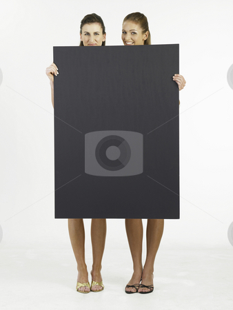 Two woman holding black card  stock photo, Two woman holding a big size card by eskaylim