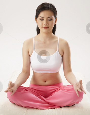 Woman meditating stock photo, Woman meditating on the plain color background by eskaylim
