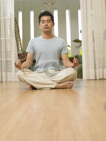 Man doing yoga stock photo, Man doing yoga at home with eye closed by eskaylim