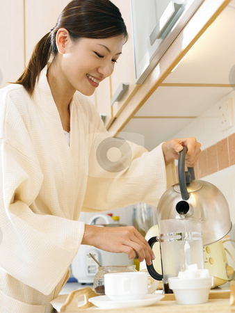 Woman in the kitchen stock photo, A lady pouring hot water into the tea pot by eskaylim