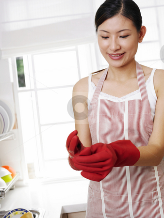 Woman doing house work stock photo, Pulling out her rubber gloves after washing the dishe by eskaylim
