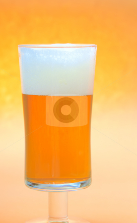 Beer glass stock photo, Close up of a beer glass with yellow beer and foam by Marek Poplawski