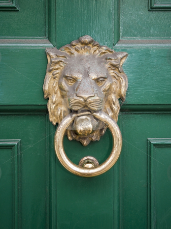 Lions head on green door stock photo, A brass lions head on a glossy green door by Mike Smith