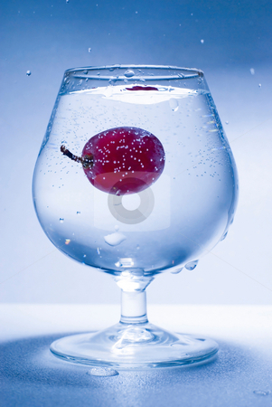 Falling grape and glass water stock photo, Glass water and falling grape by Lawren