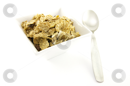 Bran Flakes in a White Bowl stock photo, Crunchy delicious looking bran flakes in a white bowl with a spoon on a white background by Keith Wilson