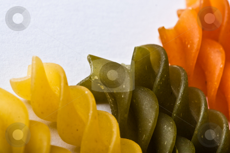 Pasta stock photo, Macro of colored raw fusilli or rotini pasta in studio by Jose Wilson Araujo