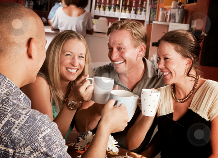 Toasting with Coffe Cups stock photo, Friends in a coffee house toasting with their cups by Scott Griessel