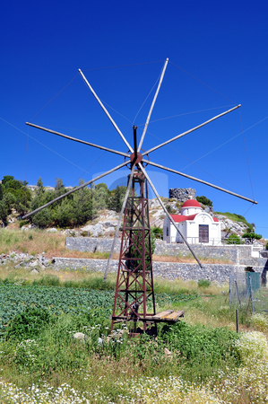 Old windmill in the Lassithi plateau, Crete stock photo, Old mill with greek chapel in the background. Crete, Greece by Fernando Barozza