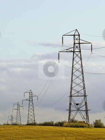 Pylons near wheat field stock photo, A row of pylons near a golden wheatfield by Mike Smith