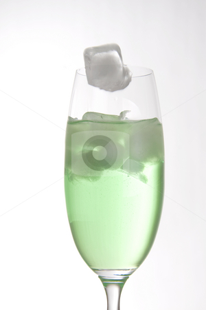 Ice cube falling stock photo, Ice cube falling into a bright green drink in a tall champagne glass by Daniel Kafer