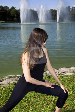 Woman doing a stretch in the park stock photo, Latina is working out in the park stretching before a run by Daniel Kafer