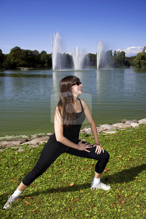 Woman stretching by the lake stock photo, Latina is working out in the park stretching before a run by Daniel Kafer