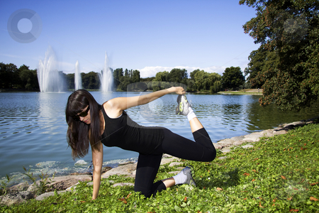 Woman stretching in front of a lake stock photo, Latina is working out in the park stretching before a run by Daniel Kafer