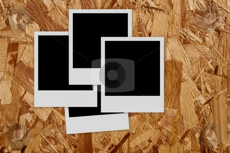 Pile of  empty photo frames  on wood background stock photo, Pile of blank polaroid films on wood background by Laurent Dambies