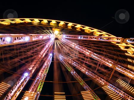 Amusement park big wheel stock photo, Spinning amusement park big wheel at night by Laurent Dambies