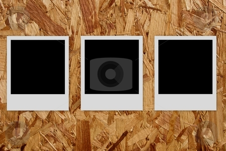 Three empty photo frames  on wood background stock photo, Three empty polaroid films on wood background by Laurent Dambies