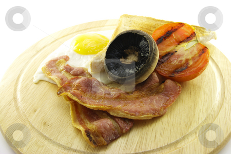 Breakfast and Toast on a Wooden Plate stock photo, Slices of crispy pork bacon with half a grilled tomato a fried egg, mushroom and a slice of toast on a white round plate with a white background by Keith Wilson