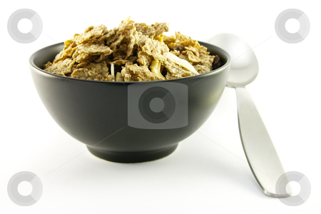 Bran Flakes in a Black Bowl stock photo, Crunchy delicious looking bran flakes in a black bowl with a spoon on a white background by Keith Wilson