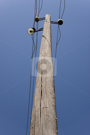 Wooden pillar stock photo, Old one wooden pillar with power line, blue sky. by Tomasz Parys