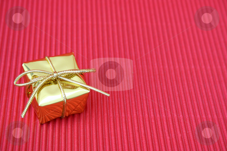 Christmas Gift stock photo, Small golden christmas gift on a red background by Vanessa Van Rensburg