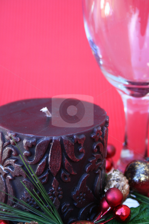 Christmas Candle stock photo, Dark candle with a christmas wreath and a wine glass on a red background by Vanessa Van Rensburg