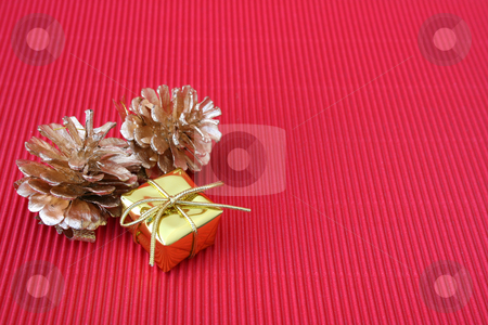 Christmas Gift stock photo, Small golden christmas gift and pine cones on a red background by Vanessa Van Rensburg