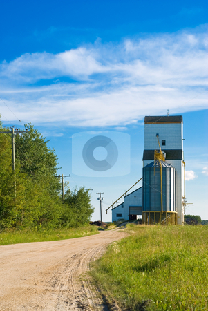 Prairie Grain Elevator stock photo, A prairie grain elevator with a dirt road running to it shot on a partly cloudy day by Richard Nelson