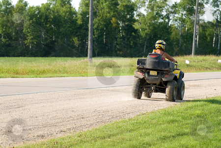 ATV stock photo, An ATV driving away down the side of a road with copyspace behind by Richard Nelson