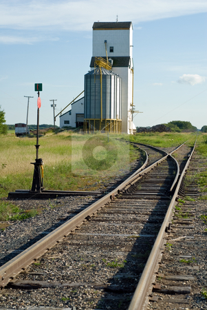 Grain Elevator Near Tracks stock photo, A grain elevator situated near a set of railroad tracks with the rails ending in a vanishing point by Richard Nelson