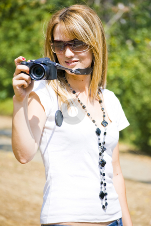 Beautiful young woman with camera stock photo, Beautiful young woman taking photos by Desislava Dimitrova
