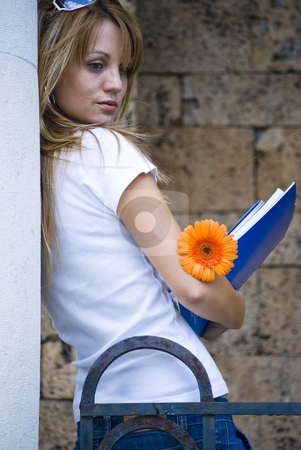 Young woman with books and flower stock photo, Beautiful young woman with books and flower outdoor by Desislava Dimitrova