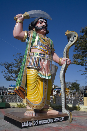 Statue of Demon Mahishasura on Chamundi Hill India stock photo, Mahishasura Mardhini, the one who vanquished the demon Mahishasura, Chamudeeswari, or Dura is the fierce form of Shakti.  Colorful gigantic image of the demon.  Found at summit of Chamundi Hill. by Sharron Schiefelbein